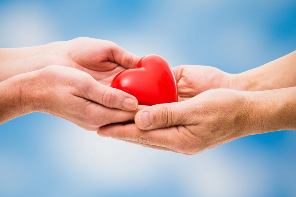 Person giving heart to another
